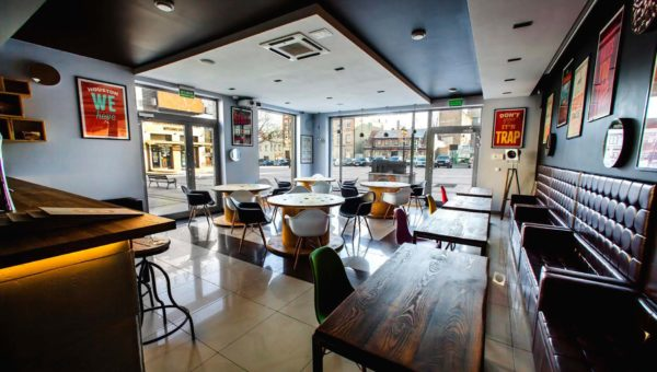 Wnętrze zaprojektowane przez Sare Tokarczyk. Modne krzesła, plakaty dominujący styl industrialny.